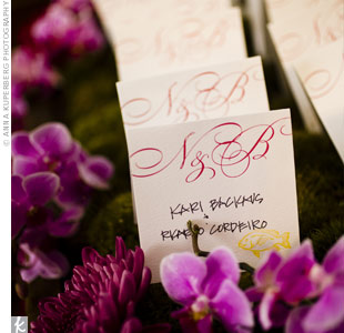 Square cards, printed with Niki and Ben's initials, set on a bed of moss among orchids and other flowers.