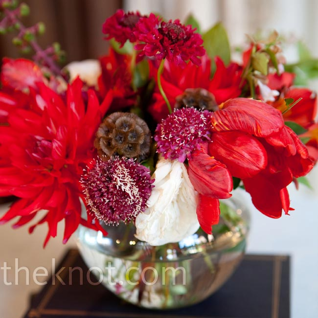 Vintage hardcover books from thrift stores served as a base for the petite red flower arrangements.