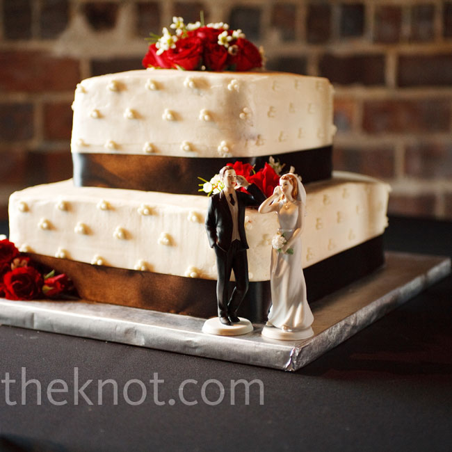 The couple chose a small red velvet cake in dotted buttercream, paired with a cheeky topper -- a bride and groom on their cell phones.