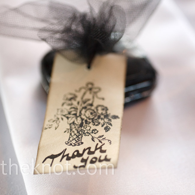Guests received two favors: First, a donation was made in their name to the ASPCA (in honor of the couple's dog, Roxie), and second, a small black mint tin rested on each place setting. The tins were wrapped in either red or black tulle and tied off with a tea-stained thank-you note.