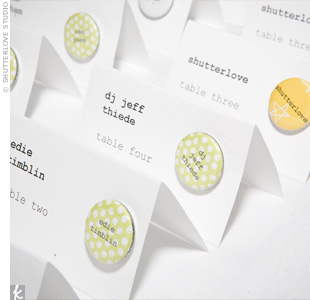 Mini pin buttons bearing each guest&#39;s full name dressed up the simple white tented escort cards.