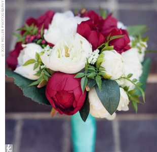 Staci arranged her own bouquet with red and cream silk peonies and ranunculus she bought online.