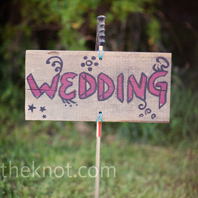 Wooden signs painted with a festive design directed guests to the reception tent.