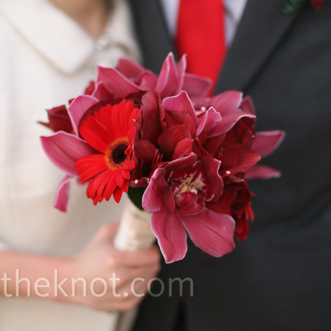 Michelle carried a bouquet of red orchids and daisies.