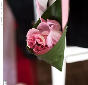Banana leaf baskets with pink rose petals adorned the inner aisle chairs.