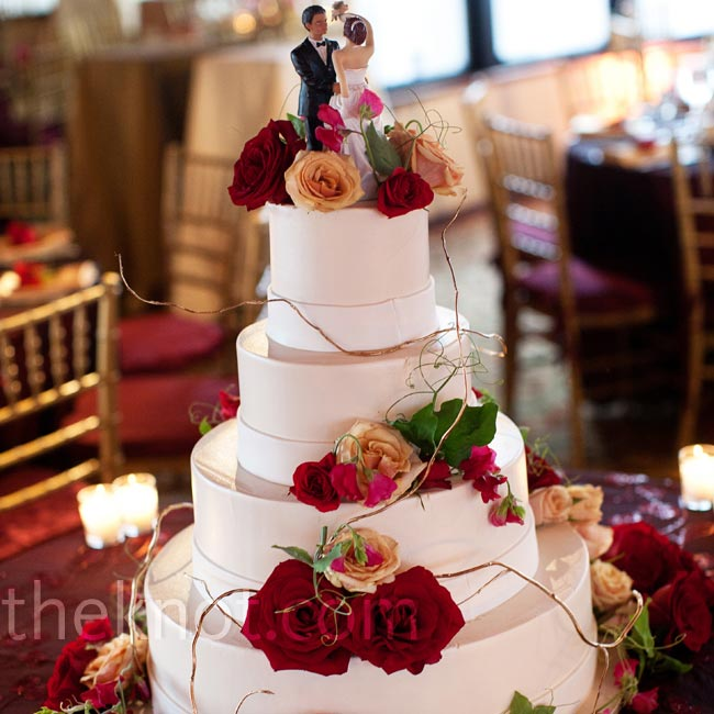 Fresh roses decorated the cake's tiers. The bride-and-groom topper actually resembled the couple.