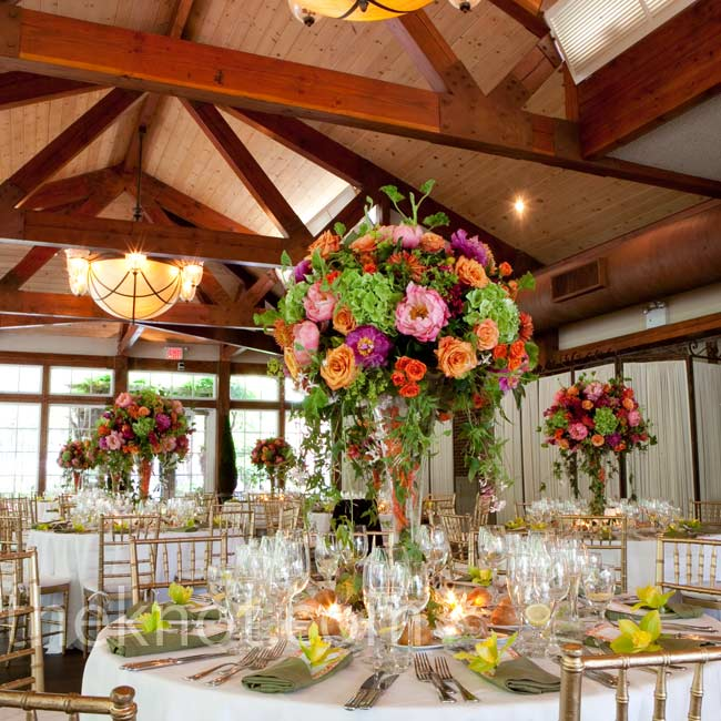 Tables were topped with tall vases filled with wild arrangements of orange and pink roses and lush green hydrangeas.