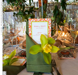 Green linen napkins and a single orchid held the orange menu cards.