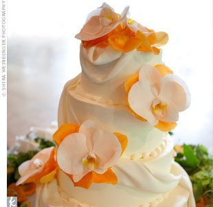 "The buttercream wedding cake was accented with fondant ""fabric draping"" and fresh flowers."