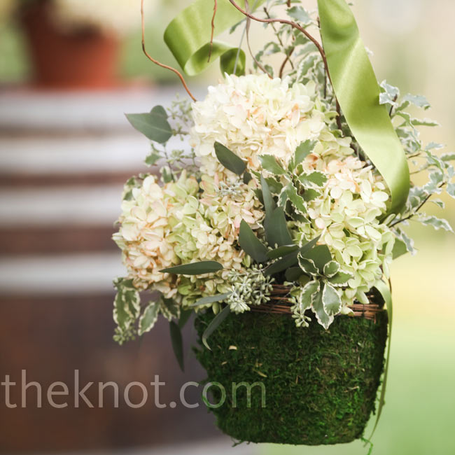 On each side of the aisle, shepherd's hooks held moss-covered baskets of hydrangeas tied with sage green ribbon.