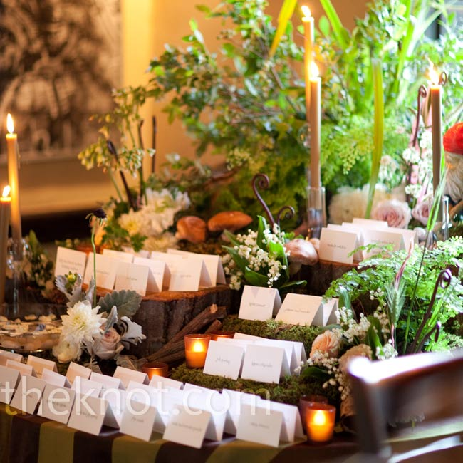 """An enchanted forest on a table,"" says Shana of the escort card display, which featured levels of greenery, flowers and candles."