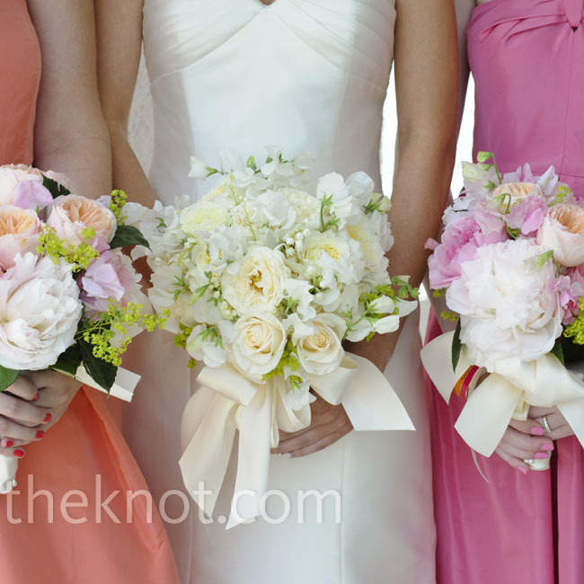 Pink and coral garden roses for the bridesmaids and white roses for the bride complemented the dresses.