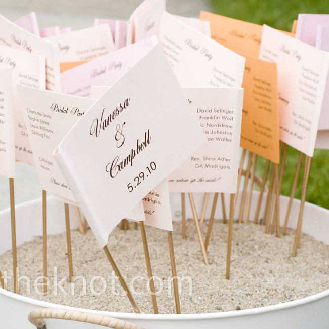 The programs were attached to mini dowel rods for guests to wave while cheering as the couple walked down the aisle.