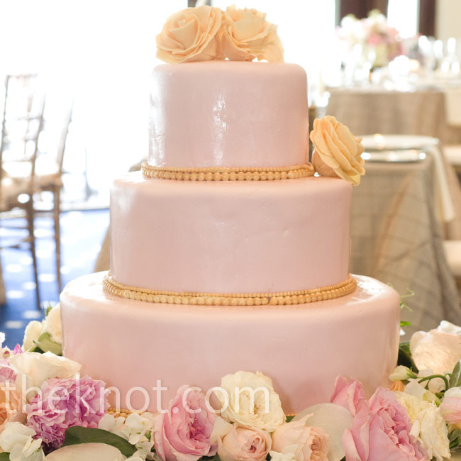 Orange sugar roses and simple buttercream pearls decorated the three-tiered pink fondant cake.