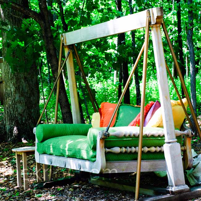 An outdoor sofa bed was covered in green fabric and topped with plump, colorful pillows that matched the wedding palette.