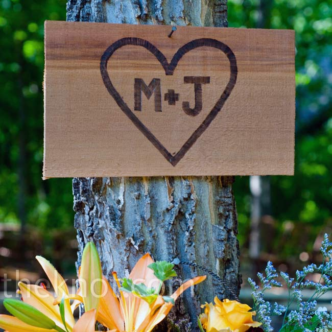 The couple's initials were painted on slabs of wood and nailed to a tree above a decorative tin filled with flowers.