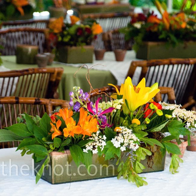 Green ceramic containers in various shapes held multicolored floral arrangements and complemented the bamboo tables with matching green linens.