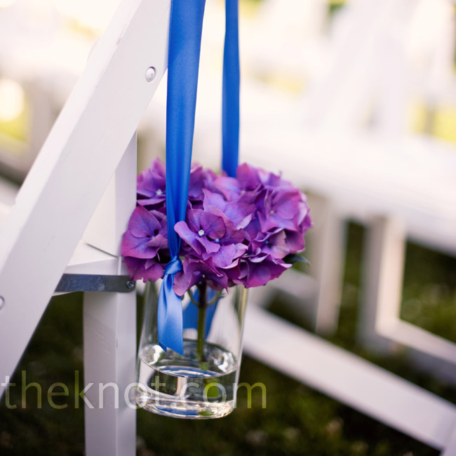 Small vases of purple hydrangeas tied with blue ribbon hung from the folding chairs, giving the ceremony a fresh, summery look.