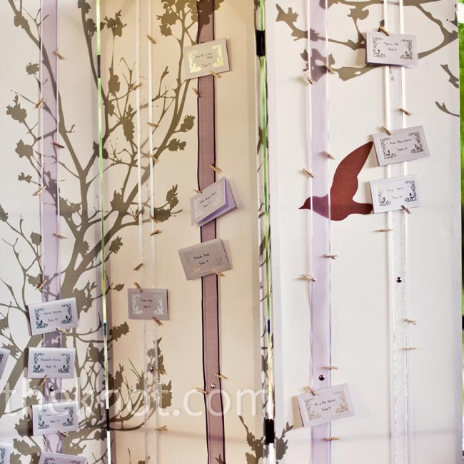 A folding screen decorated with ribbon was a creative way to display the silver and lilac escort cards.