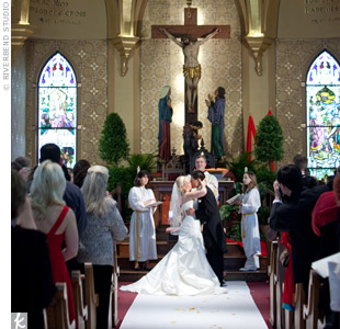 The couple kept the decor simple, with topiary plants on either side of the altar.