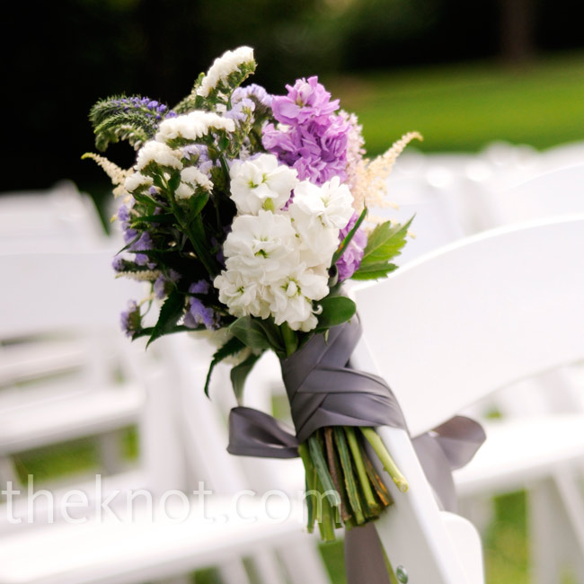 Keeping with the color scheme, bouquets of purple and white blooms were tied to the chairs.