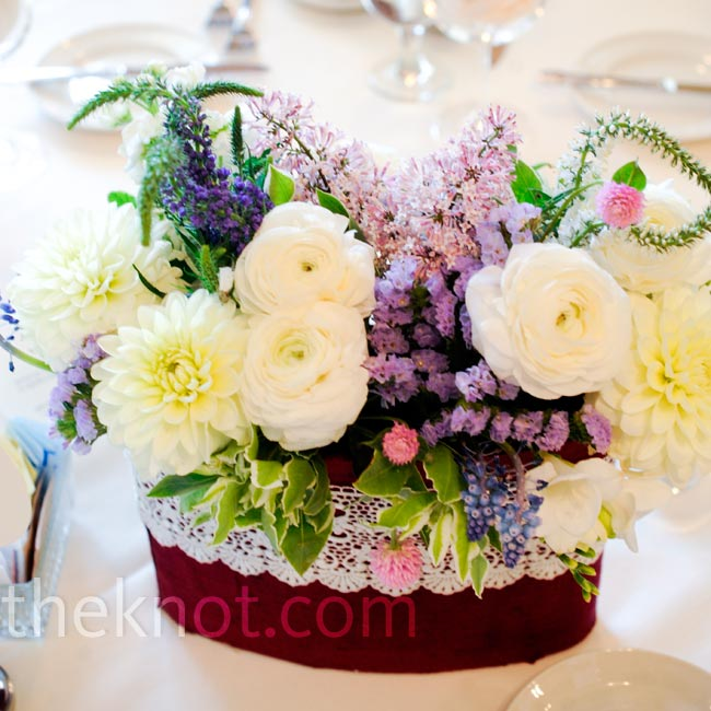 "A variety of blooms were arranged in a ""just picked"" style and displayed in silk dupioni-wrapped vases with a white lace overlays."