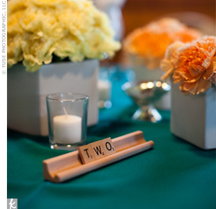 Orange and yellow carnation arrangements sat atop teal linens while Scrabble tiles spelled out the table numbers, incorporating the typography details.