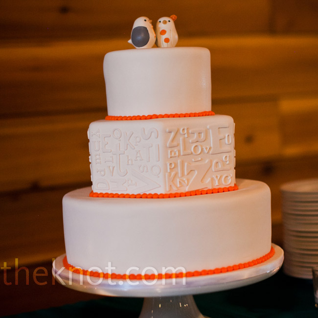 White fondant letters gave the wedding cake an embossed effect! Orange beading and sweet ceramic birds mimicked the couple's fun style.