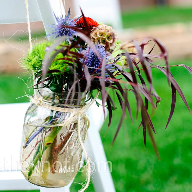 Mason jars filled with thistle, grasses and wildflowers hung from chairs lining the aisle.