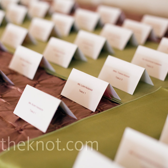 The pink and green escort cards were tented and displayed on pin-tucked fabric.