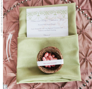 Tiny nests filled with pink jelly bean eggs were personalized with each guests name and sat atop soft green napkins.