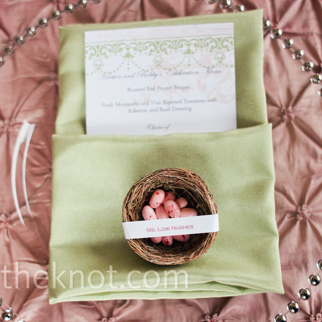 Tiny nests filled with pink jelly bean eggs were personalized with each guest's name and sat atop soft green napkins.