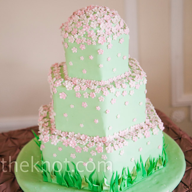 Pink sugar blossoms drifted down soft-green tiers into blades of fondant grass at the base of the cake.