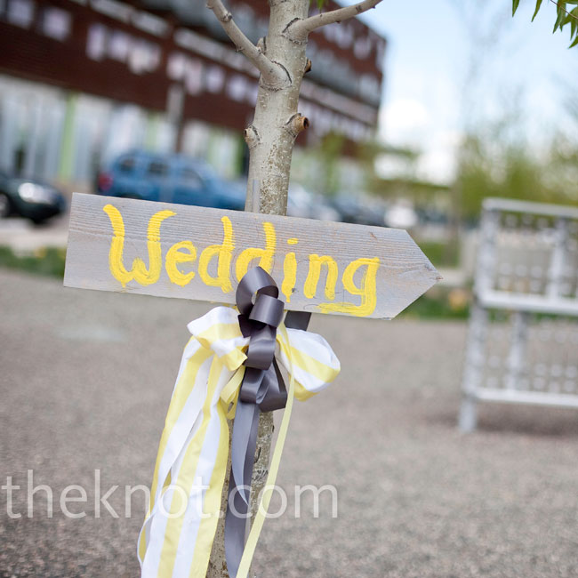 "A bright yellow ""wedding"" sign adorned with whimsical ribbon guided guests to the celebration."