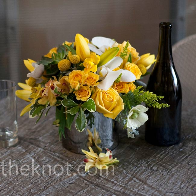 Low-lying arrangements of fragrant yellow roses, orchids, and Billy balls filled reflective, round tins next to wine bottles.