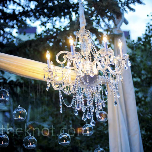 A gorgeous crystal chandelier added more drama to the candlelit outdoor wedding space.