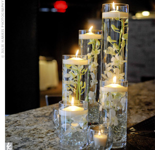 Candles floated in tall glass cylinders, revealing submerged flowers and stones.