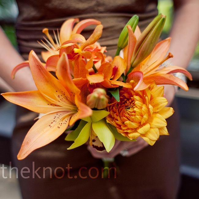 The bridesmaids monochromatic orange bouquets added a vibrant pop of color to their bronze dresses.