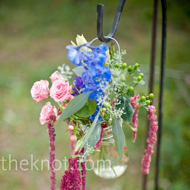 Organic arrangements of colorful flowers spilled from Mason jars that hung on shepherd hooks along the aisle.