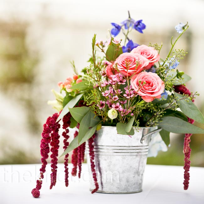 Laura wanted to use blooms that would complement the scenery. Wildflowers, tiny roses and amaranthus filled small, galvanized pails.