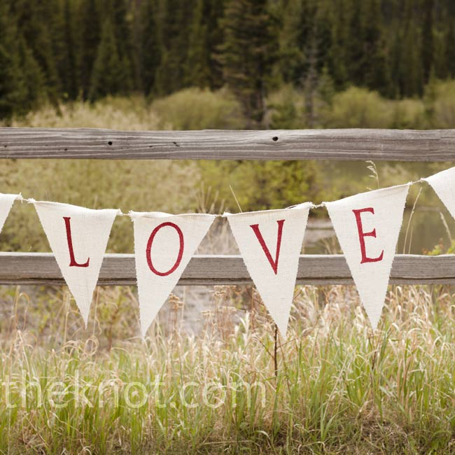 "A burlap banner spelling out the word ""Love"" marked the ceremony altar."