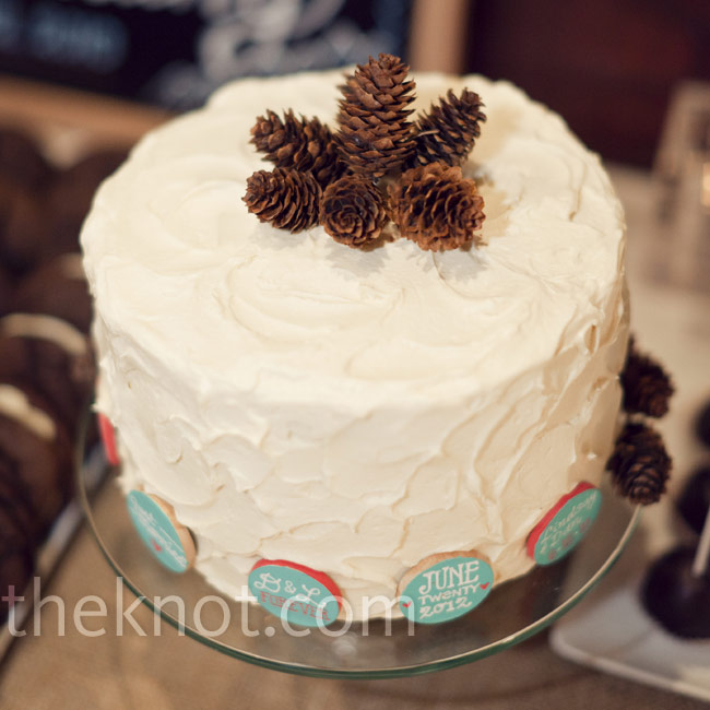 "The couple cut into a single-tiered chocolate layer cake decorated in cream cheese icing,  tiny pine cones and sayings like ""We did it!"" encircling the base."