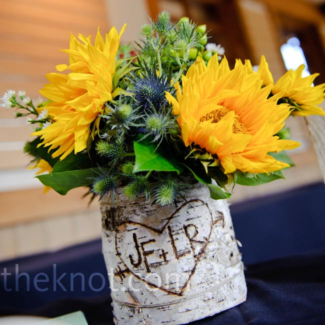 The bride's favorite flower arrangement sat on the guest book table in a birch bark vase with the couple's initials scratched into the bark.