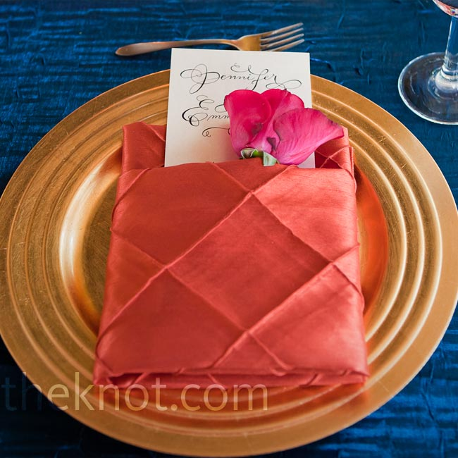 Gold chargers and coral napkins popped against the deep-blue linens.