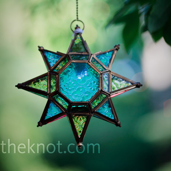 The couple hung Moroccan-inspired decor items, like this colored-glass star, from the trees in the backyard.