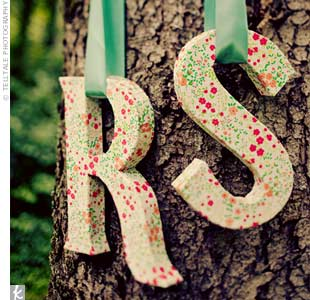 Craft letters of the couple's initials, wrapped in floral paper, hung from a tree.