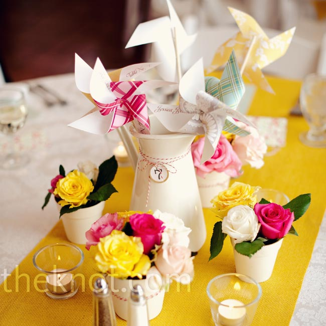 Sarah bought yellow burlap fabric and cut it down to size for the table runners. On top, each table had a pitcher of pinwheels.