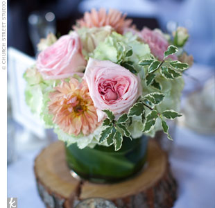 Low cylindrical vases were wrapped with ti leaves, filled with hydrangeas, roses and dahlias, and set atop a slice of wood.