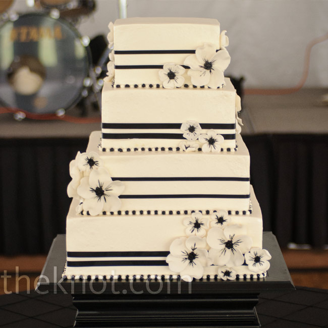 Clusters of black-and-white sugar anemones covered the cake, which was set on a sleek stand one of the groomsmen crafted.
