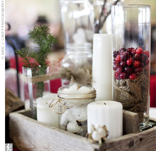 Glass cylinders and jars filled with cranberries, pine needles, cotton and candles decorated each table.